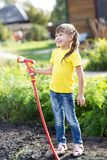 Cute toddler girl having so much fun watering in the garden. royalty free stock images