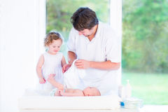Cute toddler girl helping her father to change diaper. Cute toddler girl helping her father to change a diaper and dress her newborn baby brother Royalty Free Stock Photos