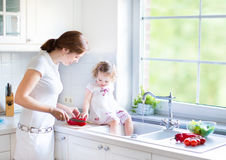 Cute toddler girl helping mother to cook vegetables Royalty Free Stock Photo