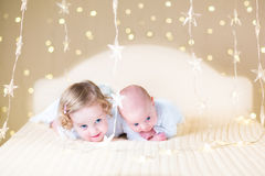 Cute toddler girl and her little newborn baby brother with warm soft lights. Cute toddler girl and her little newborn baby brother relaxing together on a white Stock Images