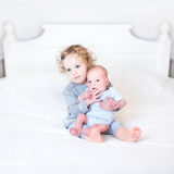 Cute toddler girl with her newborn baby brother Stock Photo