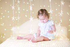 Cute toddler girl with her toy bear on a white bed between beautiful warm Christmas lights. Sweet curly toddler girl in a white dress playing with her toy bear Royalty Free Stock Photography