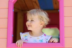 Cute toddler girl hiding in playhouse at playground Royalty Free Stock Image