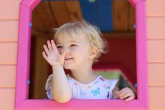 Cute toddler girl hiding in playhouse at playground Stock Photo