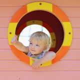 Cute toddler girl hiding in playhouse at playground Royalty Free Stock Photo