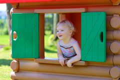 Cute toddler girl hiding in playhouse at playground Stock Photos