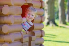 Cute toddler girl hiding in playhouse at playground Royalty Free Stock Photos