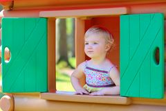 Cute toddler girl hiding in playhouse at playground Royalty Free Stock Photography