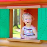Cute toddler girl hiding in playhouse at playground Stock Image