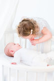 Cute toddler girl kissing the hand of her baby brother Stock Images