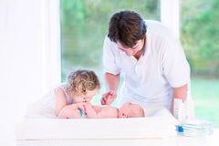 Cute toddler girl kissing her newborn baby brother. On a white changing table Stock Photos