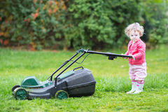 Cute toddler girl with a lawnmower in the garden Royalty Free Stock Photo