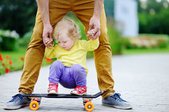 Cute toddler girl learning to skateboard with her father Stock Photos