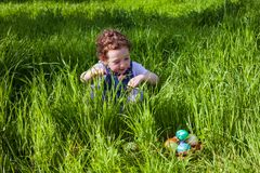 Cute toddler girl looking for eggs Royalty Free Stock Photography