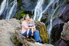 Cute toddler girl and mother sitting near water cascade of Powerscourt Waterfall, the highest waterfall in Ireland in co
