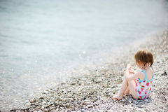 Cute toddler girl on pebble beach Royalty Free Stock Photo