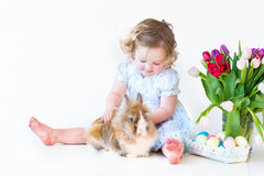 Cute toddler girl playig with a bunny on Easter Stock Photos