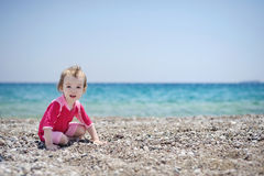 Cute toddler girl playing on a beach Stock Photos