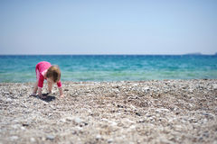 Cute toddler girl playing on a beach Stock Photo