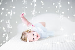 Cute toddler girl playing on a bed between Christmas lights Stock Images