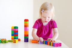 Cute toddler girl playing with colorful blocks Royalty Free Stock Images