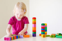 Cute toddler girl playing with colorful blocks Stock Photography