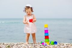 Cute toddler girl playing with colorful toys stock images
