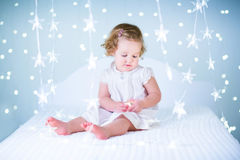 Cute toddler girl playing with her toy bear between blue Christmas lights Stock Photos