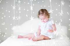 Cute toddler girl playing with her toy bear between soft lights in star shape Royalty Free Stock Photography