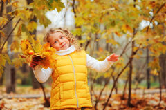 Cute toddler girl playing with leaves in autumn park on the walk. Wearing fashion yellow outfit Royalty Free Stock Images