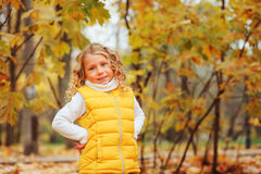Cute toddler girl playing with leaves in autumn park on the walk. Wearing fashion yellow outfit Stock Images