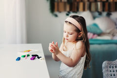 Cute toddler girl playing with plasticine or play dough at home Royalty Free Stock Images
