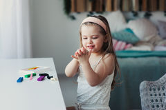 Cute toddler girl playing with plasticine or play dough at home Stock Photos