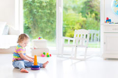 Cute toddler girl playing with a pyramid toy in a white room royalty free stock photography