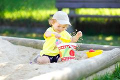 Cute toddler girl playing in sand on outdoor playground. Beautiful baby having fun on sunny warm summer sunny day. Happy. Healthy child with sand toys and in stock photos