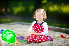 Cute toddler girl playing in sand on outdoor playground. Beautiful baby in red gum trousers having fun on sunny warm. Summer day. Child with sand toys stock photo