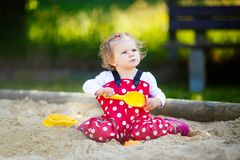 Cute toddler girl playing in sand on outdoor playground. Beautiful baby in red gum trousers having fun on sunny warm stock image