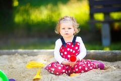 Cute toddler girl playing in sand on outdoor playground. Beautiful baby in red gum trousers having fun on sunny warm. Summer day. Child with colorful sand toys stock photography