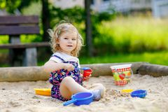 Cute toddler girl playing in sand on outdoor playground. Beautiful baby in red trousers having fun on sunny warm summer stock photography