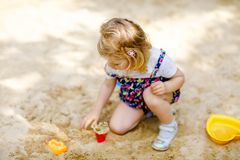 Cute toddler girl playing in sand on outdoor playground. Beautiful baby in red trousers having fun on sunny warm summer royalty free stock photo