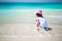 Cute toddler girl playing in shallow water at exotic beach Royalty Free Stock Photo