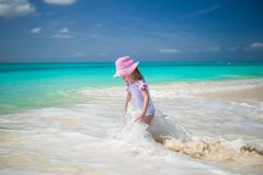 Cute toddler girl playing in shallow water at. Cute toddler girl standing in shallow water at exotic beach Stock Photos