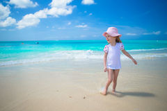 Cute toddler girl playing in shallow water at. Cute toddler girl standing in shallow water at exotic beach Royalty Free Stock Photo