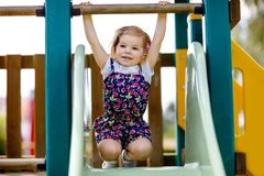 Cute toddler girl playing on slide on outdoor playground. Beautiful baby in colorful shorts trousers having fun on sunny stock photos