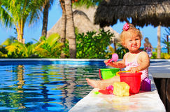 Cute toddler girl playing in swimming pool at the Stock Image