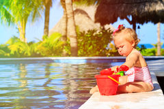 Cute toddler girl playing in swimming pool at the Royalty Free Stock Image