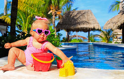 Cute toddler girl playing in swimming pool. At tropical beach Royalty Free Stock Photo