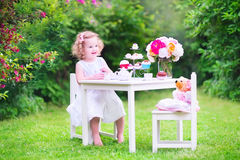 Cute toddler girl playing tea party with a doll. Adorable toddler girl with curly hair wearing a colorful dress on her birthday playing tea party with a teddy Royalty Free Stock Photo