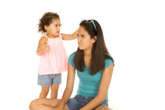 Cute toddler girl reaching for teenage sister's sunglasses Stock Image