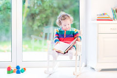 Cute toddler girl reading a book in rocking chair Stock Photography